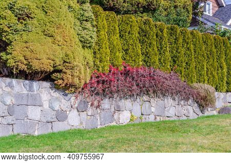 Fence built from trees and stones. Outdoor landscape. Security and privacy concept. Vancouver. Canada.