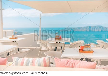 Greek Tavern Concept. Modern Outdoor Restaurant, White Design Table And Chairs With Sea View. Romant