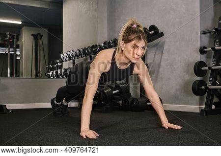 A Woman In Sportswear Stands In The Plank Pose. Sportswear. Gym.