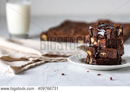A Close Up Of A Chocolate Brownie Stack Covered In Chocolate Sauce Served With A Glass Of Milk.