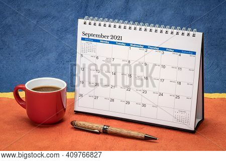 September 2021 - spiral desktop calendar against abstract paper landscape with a cup of coffee, time and business concept