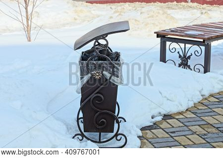 One Brown Metal Urn With An Iron Wrought Pattern Stands On The Sidewalk In A Snowdrift Of White Snow