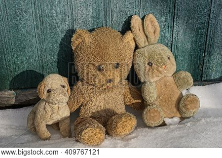 Three Old Plush Toys On A White Snowdrift Near A Green Wooden Wall On A Winter Street