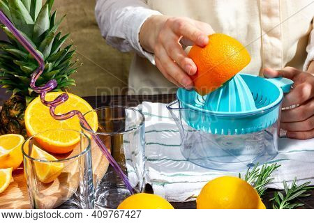 The Bartender Squeezed An Orange On A Juicer. The Process Of Making Freshly Squeezed Orange Juice. T