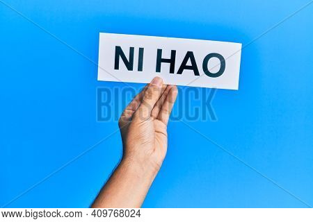 Hand of hispanic man holding chinese greeting ni hao word paper over isolated blue background.