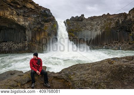 Tourist Sits At The Aldeyjarfoss Waterfall In Northern Iceland. It Is Situated In The Highlands Of I
