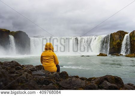 Tourist In A Yellow Jacket Relaxing At The Godafoss Waterfall In Iceland. Godafoss Means The Waterfa