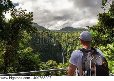 Tourist Looking At The La Fortuna Waterfall In Costa Rica. The Waterfall Is Located On The Arenal Ri