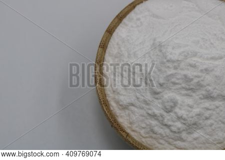 Baking Soda In Wooden Bowl On Background.
