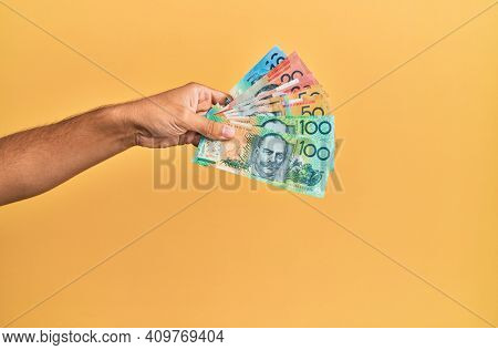 Hand of hispanic man holding australian dollars banknotes over isolated yellow background.