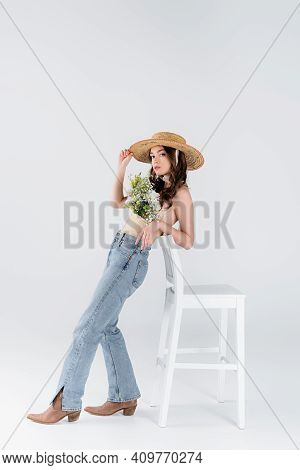 Trendy Model With Flowers In Blouse Standing Near Chair On Grey Background.