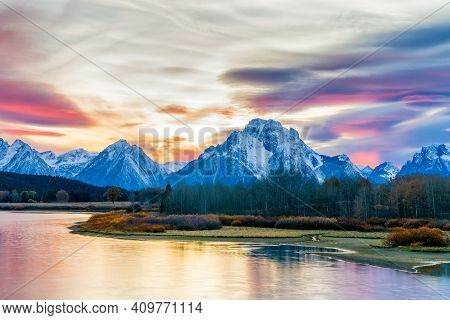 Picturesque View Of The Grand Tetons Glowing Blue In This Autumn Sunset. Beautiful Reflections A Smo