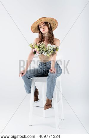 Woman With Bouquet In Blouse Looking At Camera While Sitting On Chair On Grey Background.