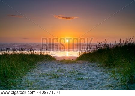 Perfectly Centered Sun Sitting On The Horizon Leads The Eye Down The Beach Path To The Colorful Ocea