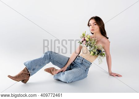 Young Stylish Model With Flowers In Blouse Sitting On Grey Background.