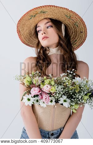 Curly Model In Sun Hat With Flowers In Blouse Looking Away Isolated On Grey.