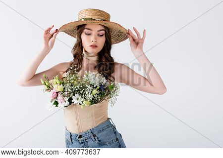 Trendy Woman Holding Sun Hat And Posing With Different Flowers In Blouse Isolated On Grey.