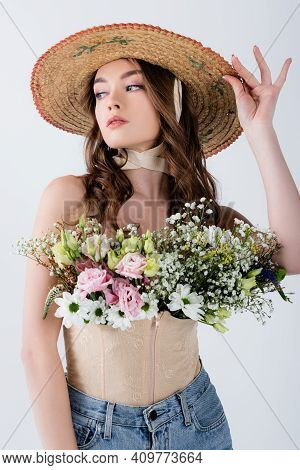 Stylish Woman In Sun Hat And Flowers In Blouse Isolated On Grey.