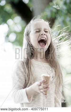 Ice Cream Makes Her Fall Into Euphoria. Cute Little Girl Eating Ice Cream On Summer Day. Small Child