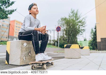 Teenager Skateboarder Boy In Baseball Cap Riding A Skateboard On Asphalt Street Road. Youth Generati