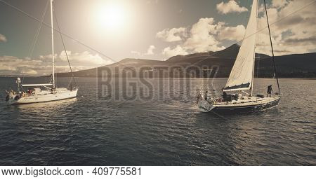 Sun over sailing regatta on luxury yachts aerial. Cinematic seascape of yachting summer sunny day. Panorama drone shot. Majestic sail boats race at ocean bay in Brodick harbour, Arran Island, Scotland