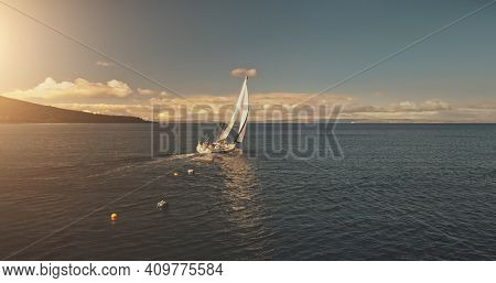 Aerial yacht regatta race at open sea. White sail boat at summer sunlight day. Amazing seascape of ocean waters at sun reflections. Serene water at cinematic relax and calm waterscape