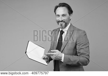 Happy Man In Suit With Book. Accountant Maintains Accounting Records. Making Notes In Notebook. View