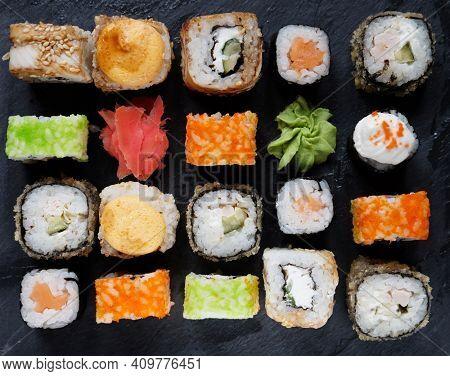 Japanese sushi food. Maki ands rolls with tuna, salmon, shrimp, crab and avocado. Top view of assorted sushi. Rainbow sushi roll, uramaki, hosomaki and nigiri.
