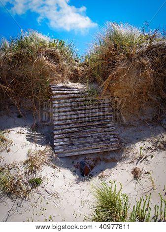 Collapsed timber boardwalk on sand erosion beach