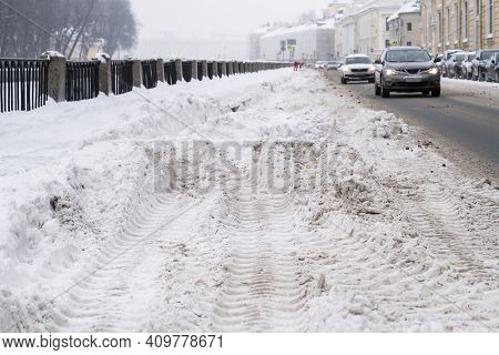 Uncleaned Street With Heavy Snowdrifts After Snowfall In The City, Cars On The Road On Background. W