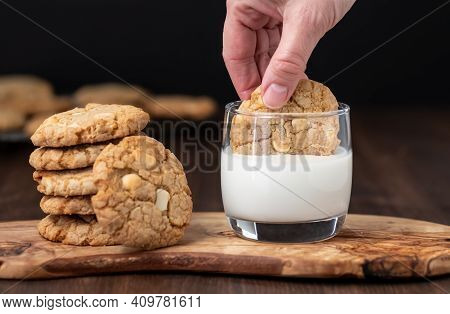 Close Up Of A Hand Dunking A White Chocolate Chip And Macadamia Nut Cookie Into A Glass Of Milk.