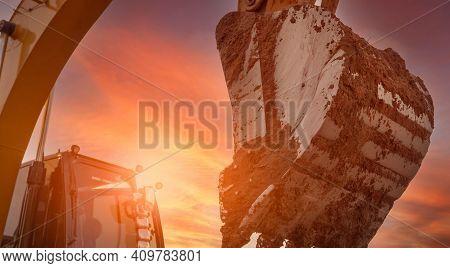 Backhoe Digging Soil At Construction Site. Dirt Bucket Of Backhoe Digging Soil With Yellow Sunset Sk