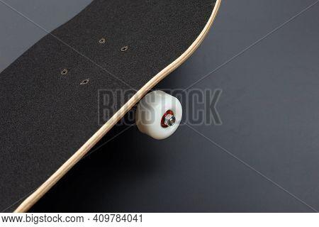 Black Skateboard On Dark Background. Top View