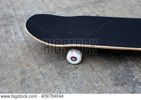 Black Skateboard On Cement Or Concrete Ground.