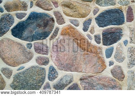 The Wall Is Made Of Natural Stone And Cement. Fragment Of A Colored, Textured Stonewall. Bright Back