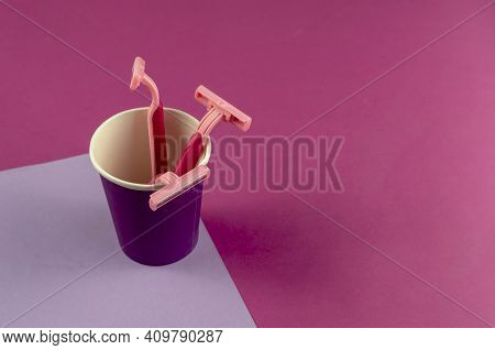 Pink Plastic Razors In A Lilac Glass On A Pink And Light Lilac Background. Three New Ladies' Razors