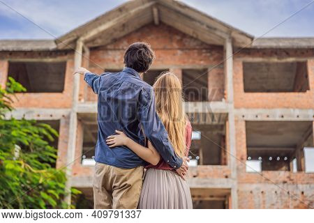Couple Looking At Their New House Under Construction, Planning Future And Dreaming. Young Family Dre