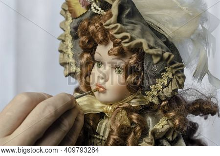 Hand Carefully Paints The Doll's Lips With A Thin Brush. Doll In A Vintage Style. Concept Of Combini