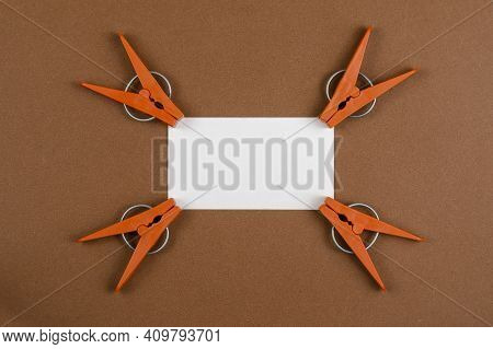 Brown Plastic Clothespins And White Blank Business Card On Brown Background. New Clothespins Around