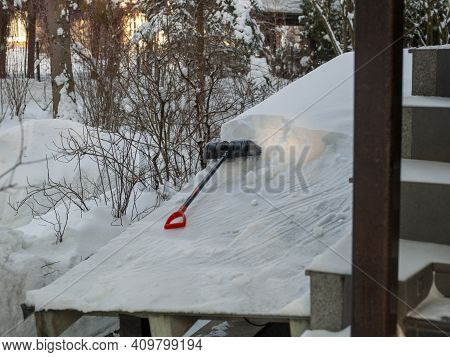 Removing Snow From A Ledge Outside A House, Abandoned Shovel In The Center Of Composition