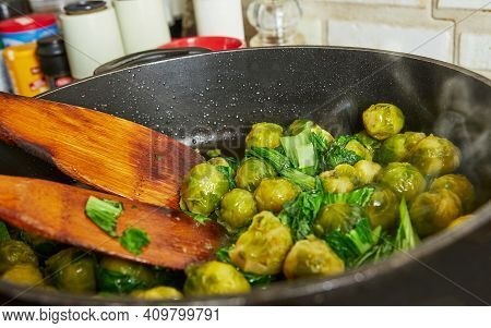Cooking At Home In The Kitchen According To Recipe From The Internet. Brussels Sprouts Are Fried In