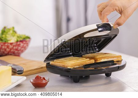 Hand Carefully Opening A Sandwich Maker With Hot Sandwiches