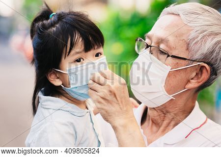 Adults And Children Wear Medical Face Mask. Grandfather Takes Care Of Granddaughter With Love And Be