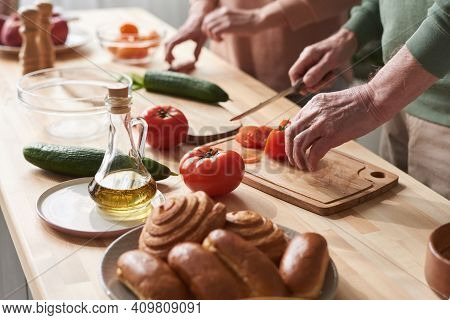 Close-up Of Couple Cutting Fresh Vegetables On Cutting Board They Preparing Salad At The Kitchen Tab