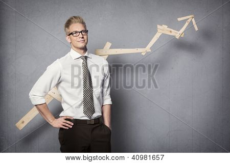 Concept: Positive business outlook. Smiling confident businessman with business vision in front of business graph with positve trend, isolated on grey background.