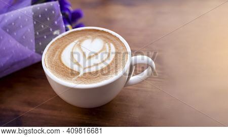 A Cup Of Fragrant Coffee With Milk In A White Cup. Drawing From Coffee Foam, A Bouquet Of Flowers On