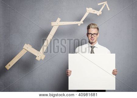 Concept: Positive business outlook. Smiling confident businessman holding empty panel in front of business graph with rising trend, isolated on grey background.