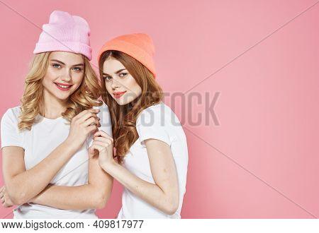 Two Women Fashionable Clothes Glamor Companionship Hug Pink Background