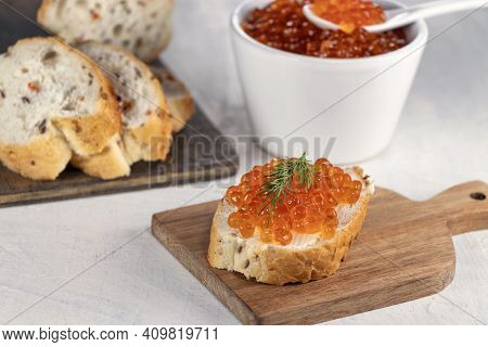 Cooking Process Snack With Red Caviar. Baguette, Red Caviar, Dill On White Background.recipe For Mak