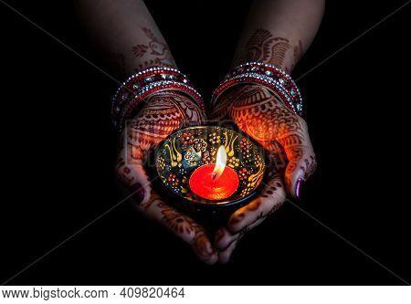 A Woman Hand Holding Diya, Mehdi Design On Woman Hand,